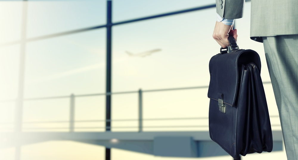 Back view of businessman at airport with suitcase in hand.jpeg
