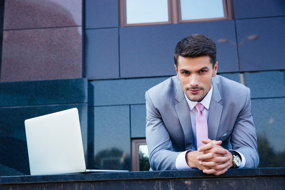 Portrait of a confident businessman with laptop computer outdoors. Looking at camera-1